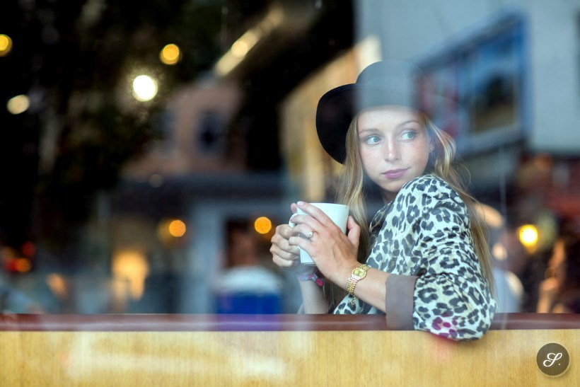 Cynthia Kamprath sitting in a cafe on a rainy day in Berlin wearing a leopard coat and hat.