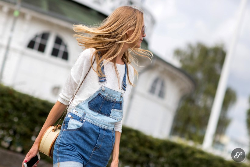 Cecilie Arling wearing a denim overall on a street style photo taken during CPHFW Copenhagen Fashion Week summer 2014.