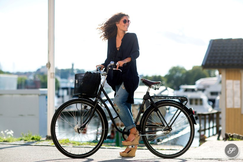 Swedish fashion blogger Emma Mattson from Freshnet caught on a street style photo while on her bike during Mercedes-Benz Fashion Week Stockholm August 2014.