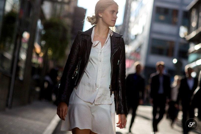 Olivia Wideroth wearing white shirt and skirt and a brown leather jacket on a street style photo taken in the streets of Stockholm.