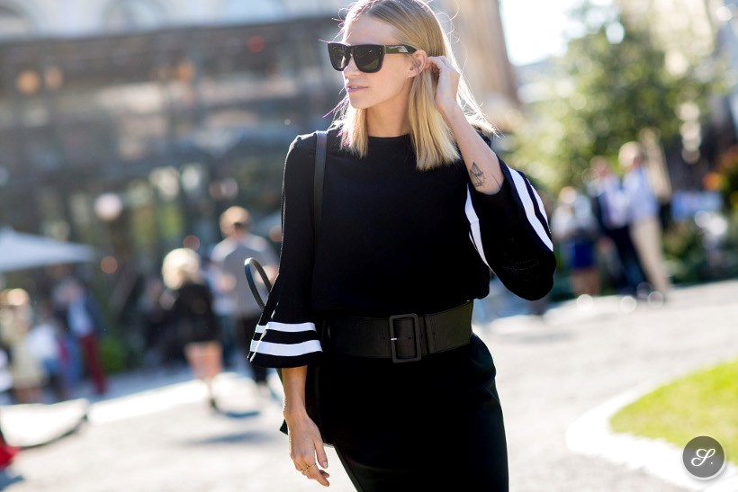 Tine Andrea Lauvli wearing a black dress with white stripes and belt on a street style photo taken during Stockholm Fashion Week summer 2014.