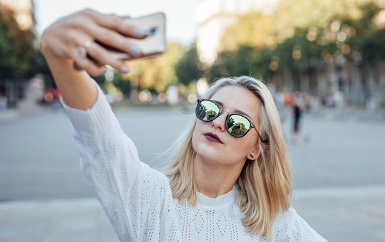 Young woman is taking a selfie by mobile phone