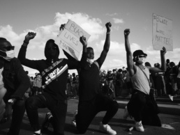 Grayscale photo of men in black t-shirt and pants holding black lives matter signs