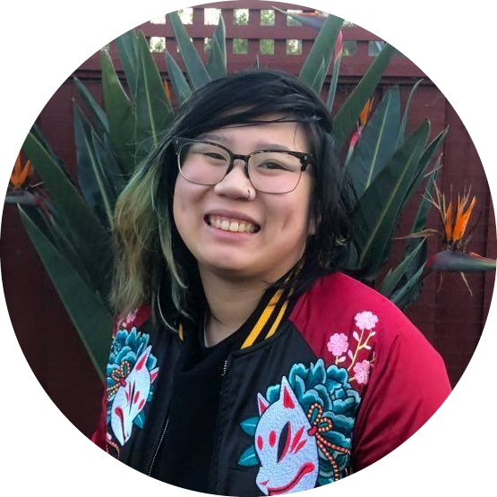 Collette is an Asian person with black and green hair pushed to the side. She wears glasses and a bomber jacket with colorful embroidery. She smiles at you. Behind them is a dark green cactus.