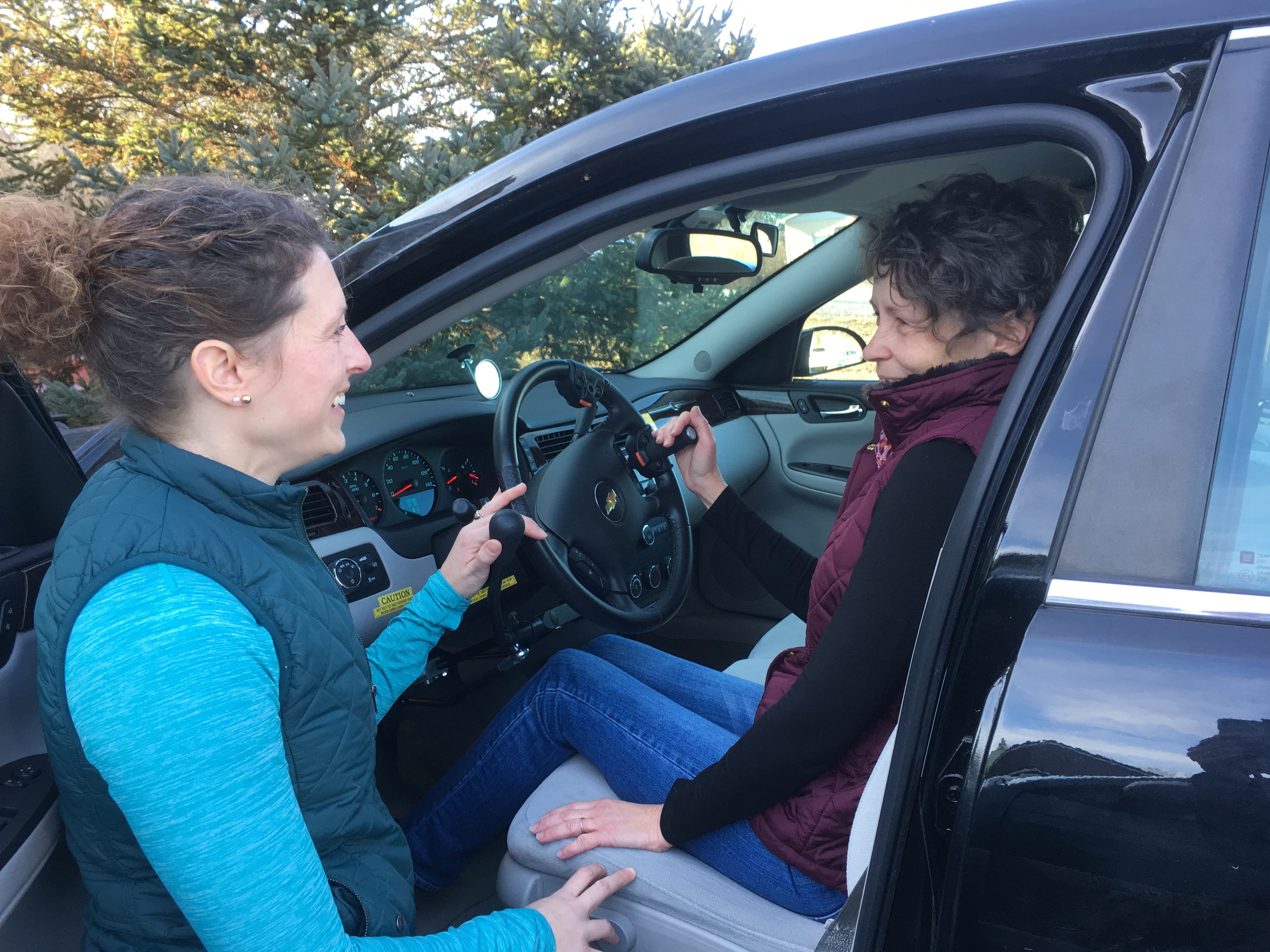 Driver rehab specialists showing a driver how to use hand controls. Driver