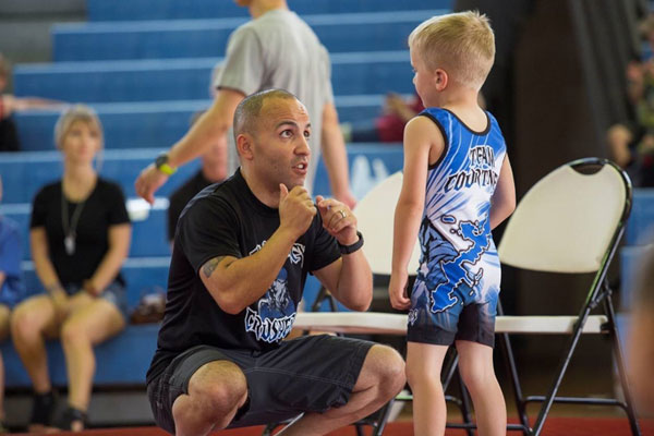 Parent squatting level with child giving coaching tips