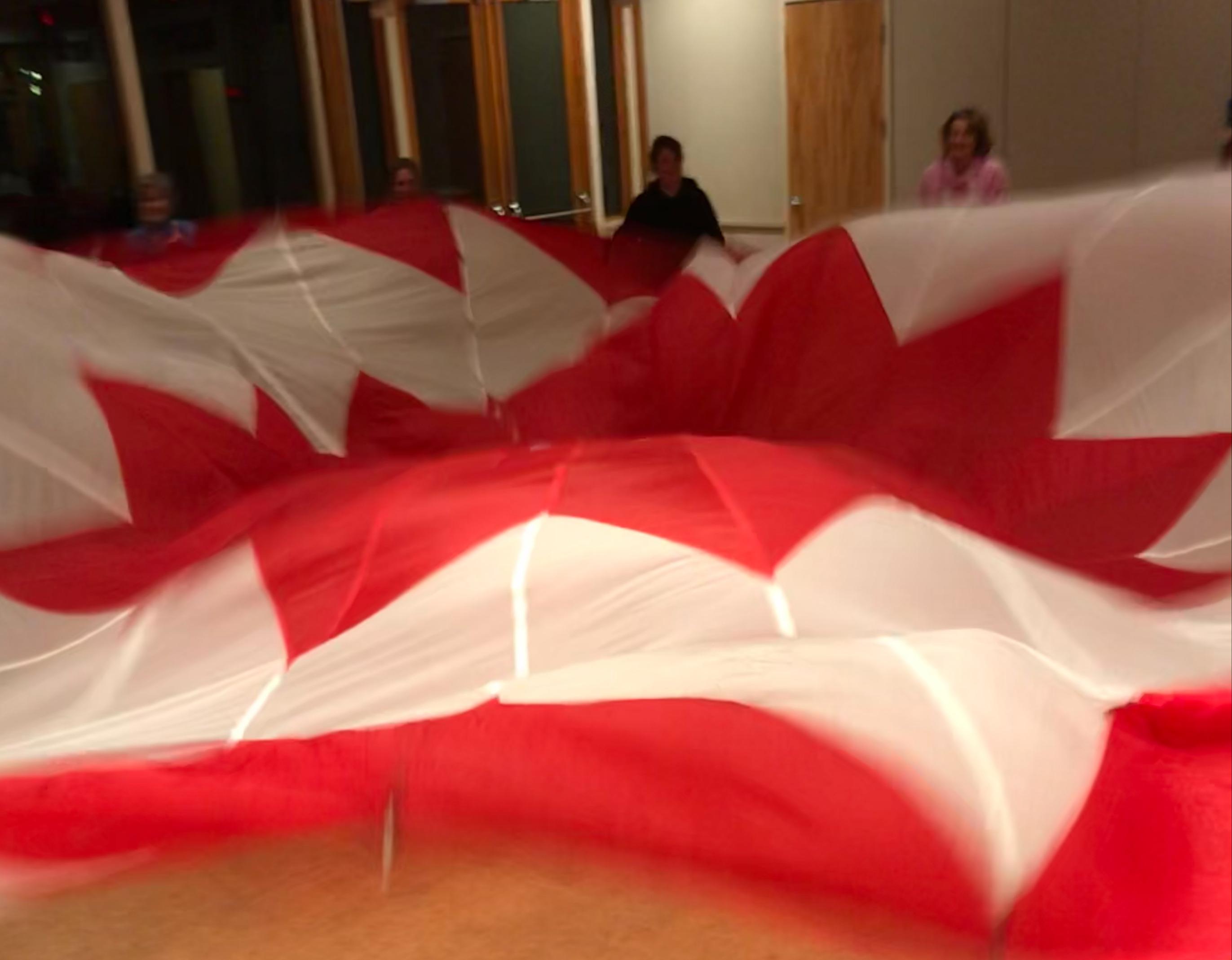 image of women shaking large parachute