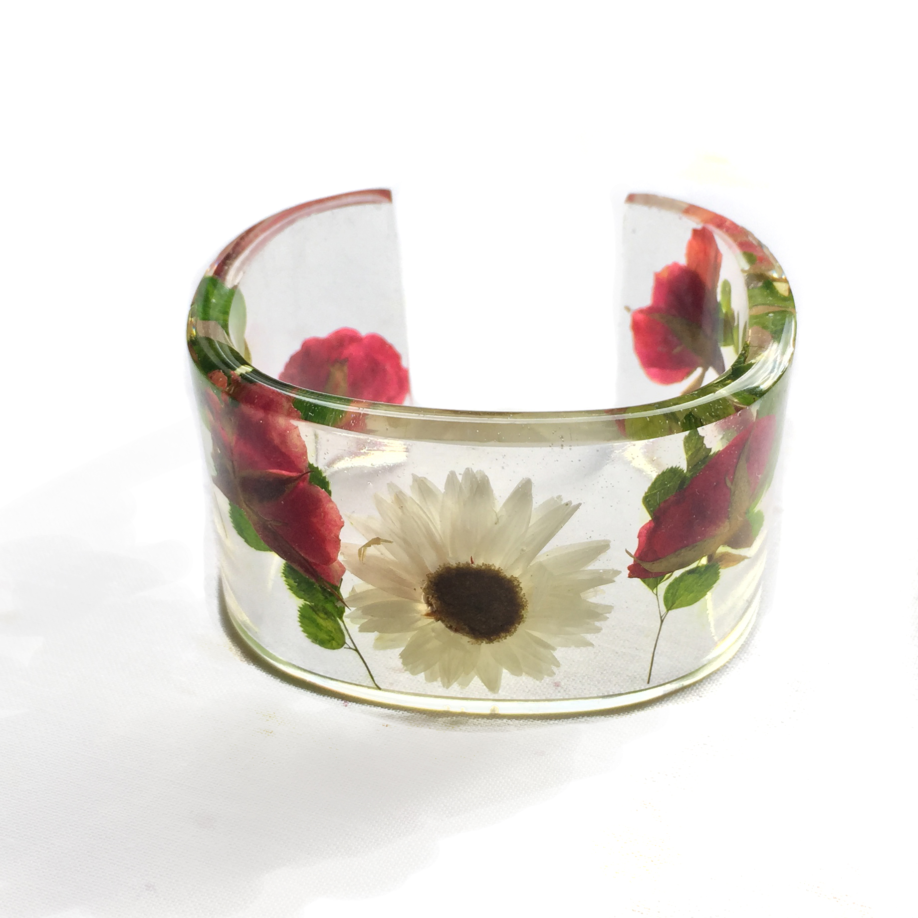 Clear resin bangle filled with white daisies and red rose buds