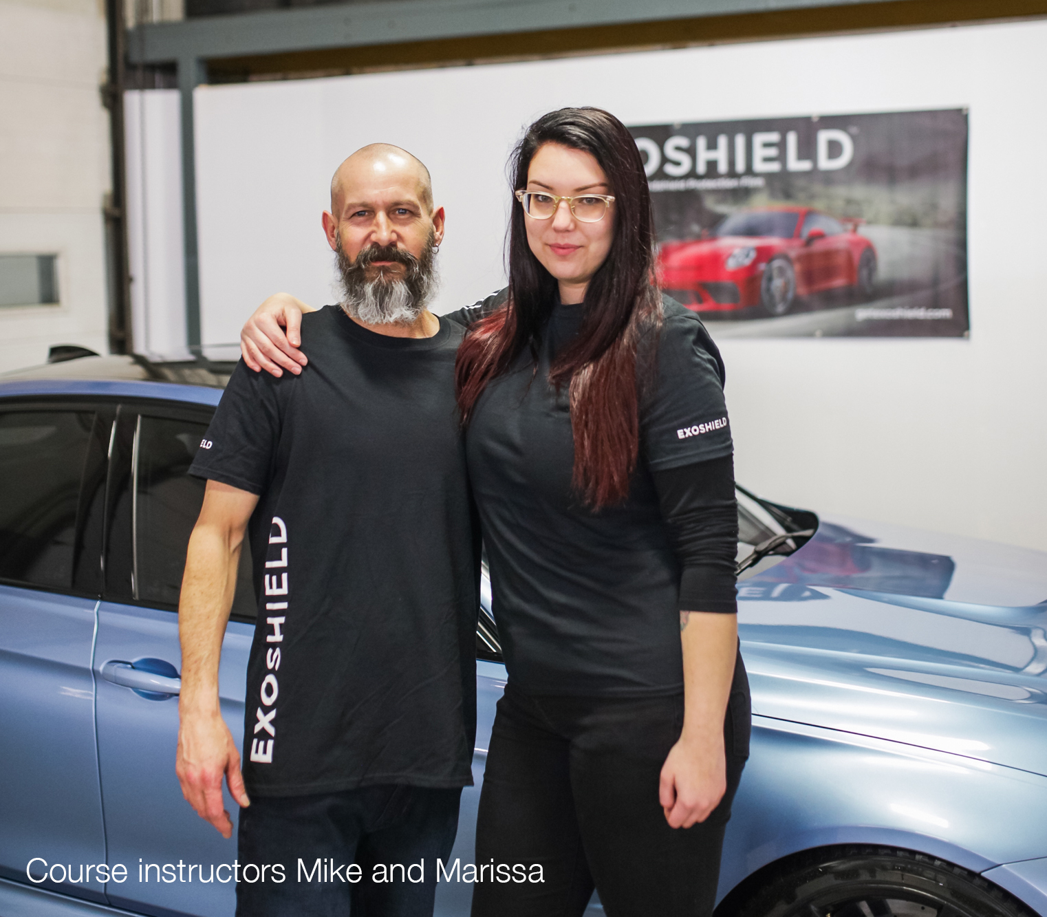 ExoShield master training Mike and host Marissa standing in front of a beautiful BMW M3.