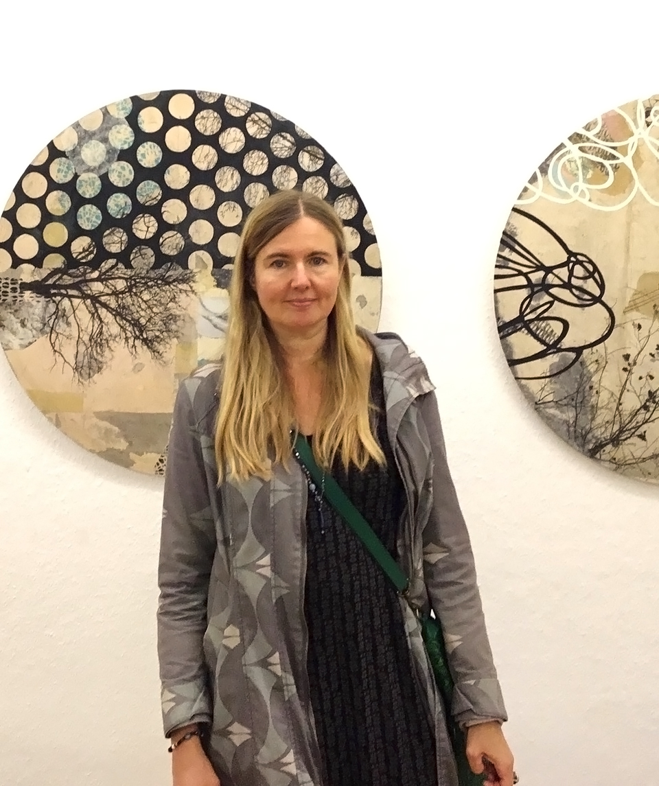 Cordula standing infront of collage artwork