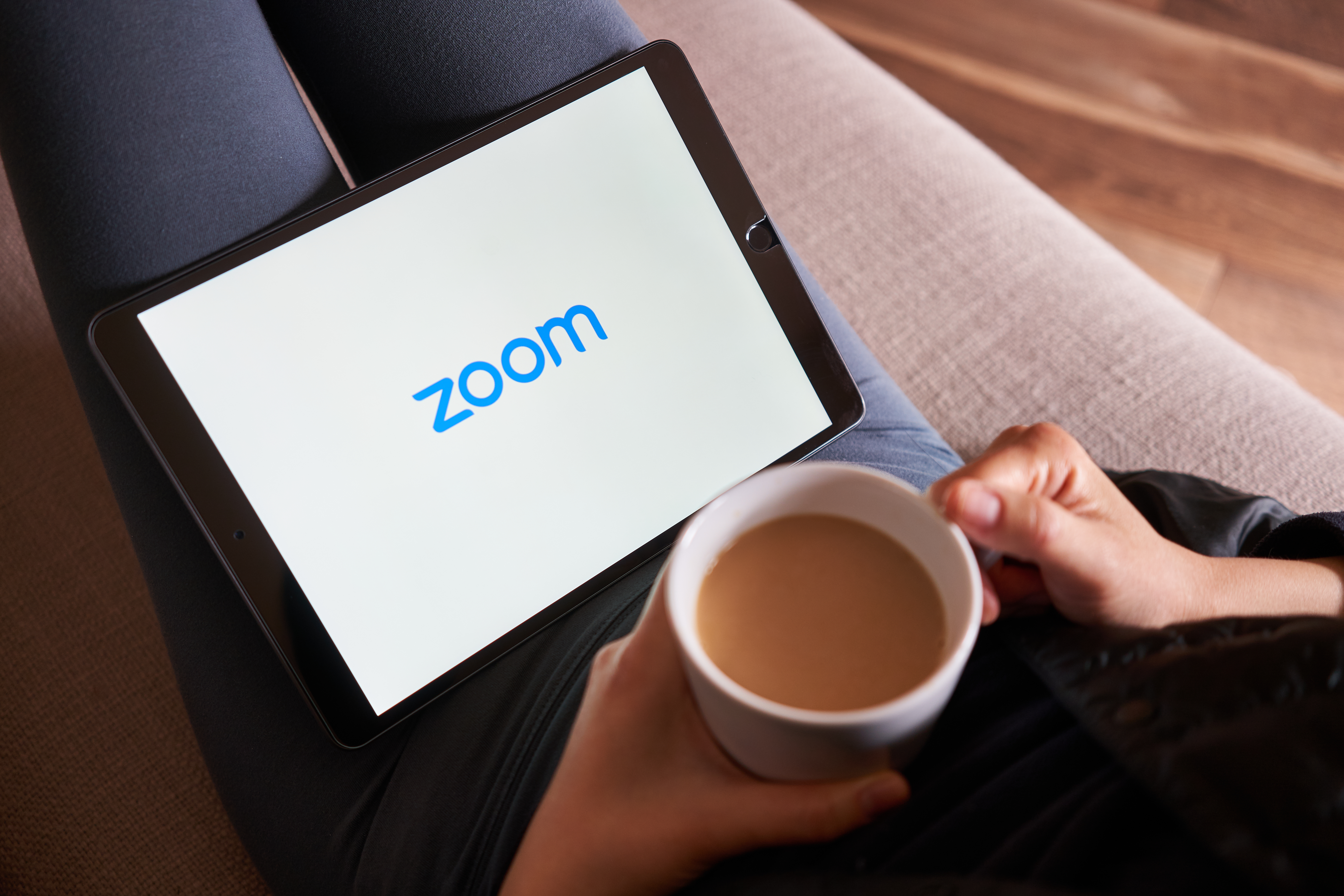 lady relaxing with a cup of tea while she joins a Zoom conference on her laptop.
