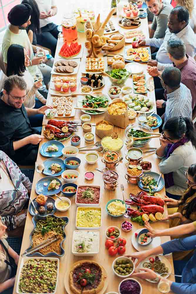 large wooden table covered with food and beverage and people sitting around it.
