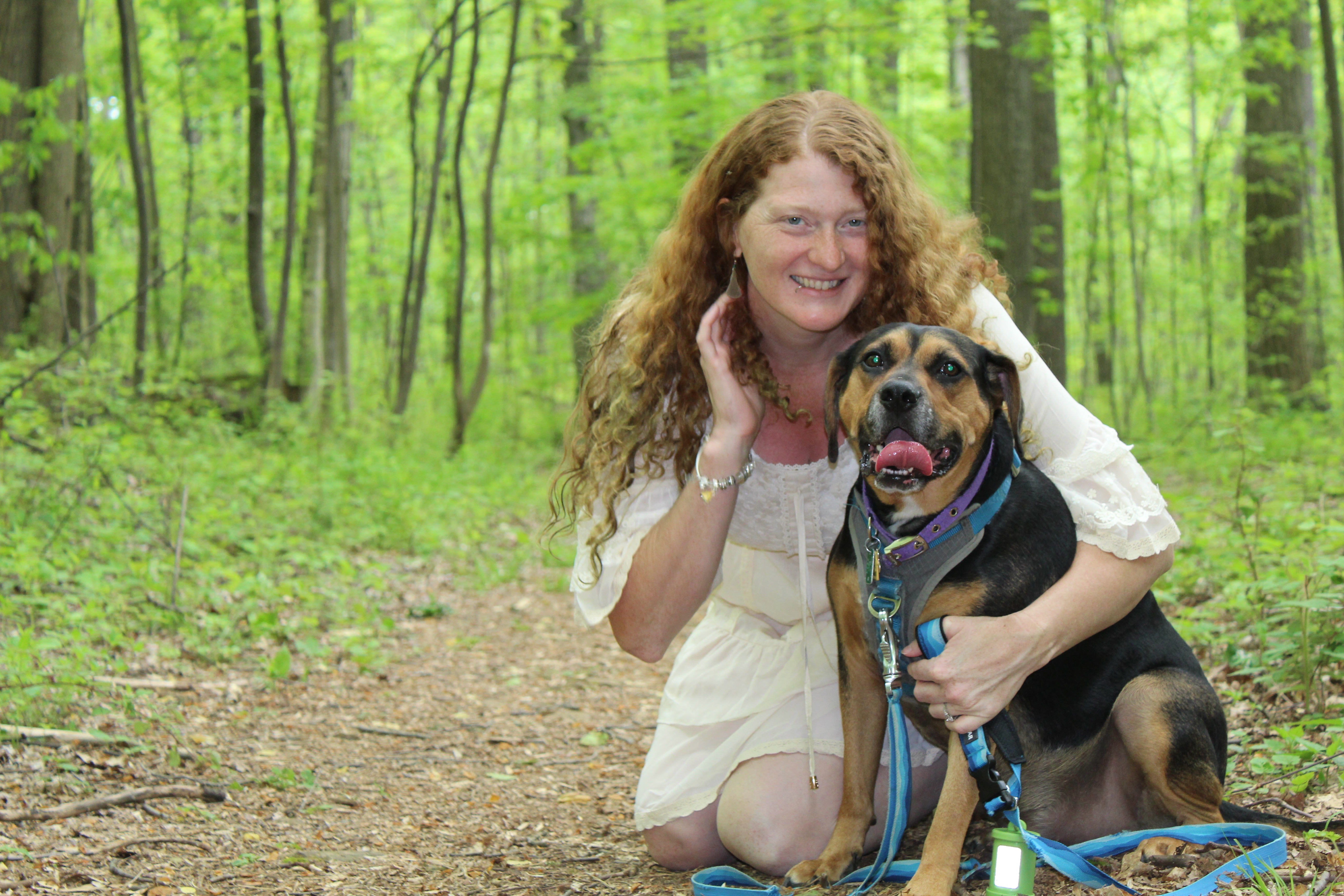 An image of Annalisa kneeling in the woods, hugging Benji, a black and tan hound dog.