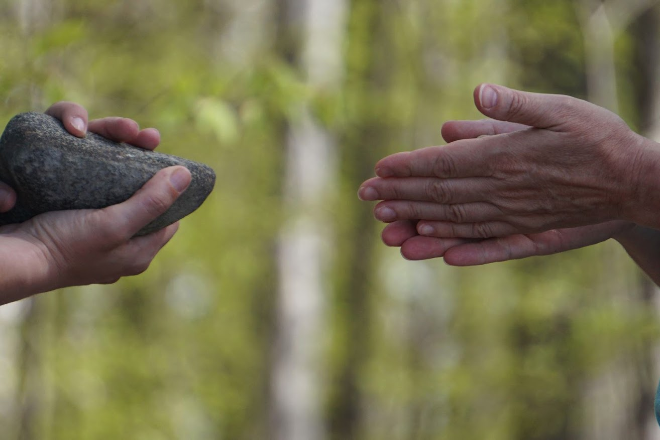 One person reverently hands a stone to another person. They are in a forest.