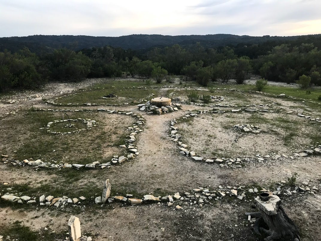 A mandala made of stones arranged on a hill top. a place where people do