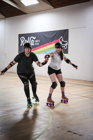 Two white female rollerskaters smiling skate hand in hand in a gym with the Rolla Skate Club banner beyond