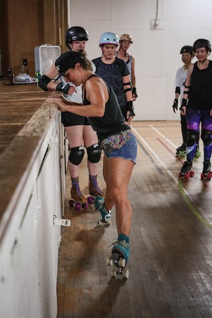 A group of female rollerskaters observe while another woman demonstrates a heel truck balance on rollerskates