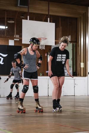 Two white female rollerskaters stand side by side in a gym. One is demonstrating for the other, wearing a GRR POWER t-shirt.