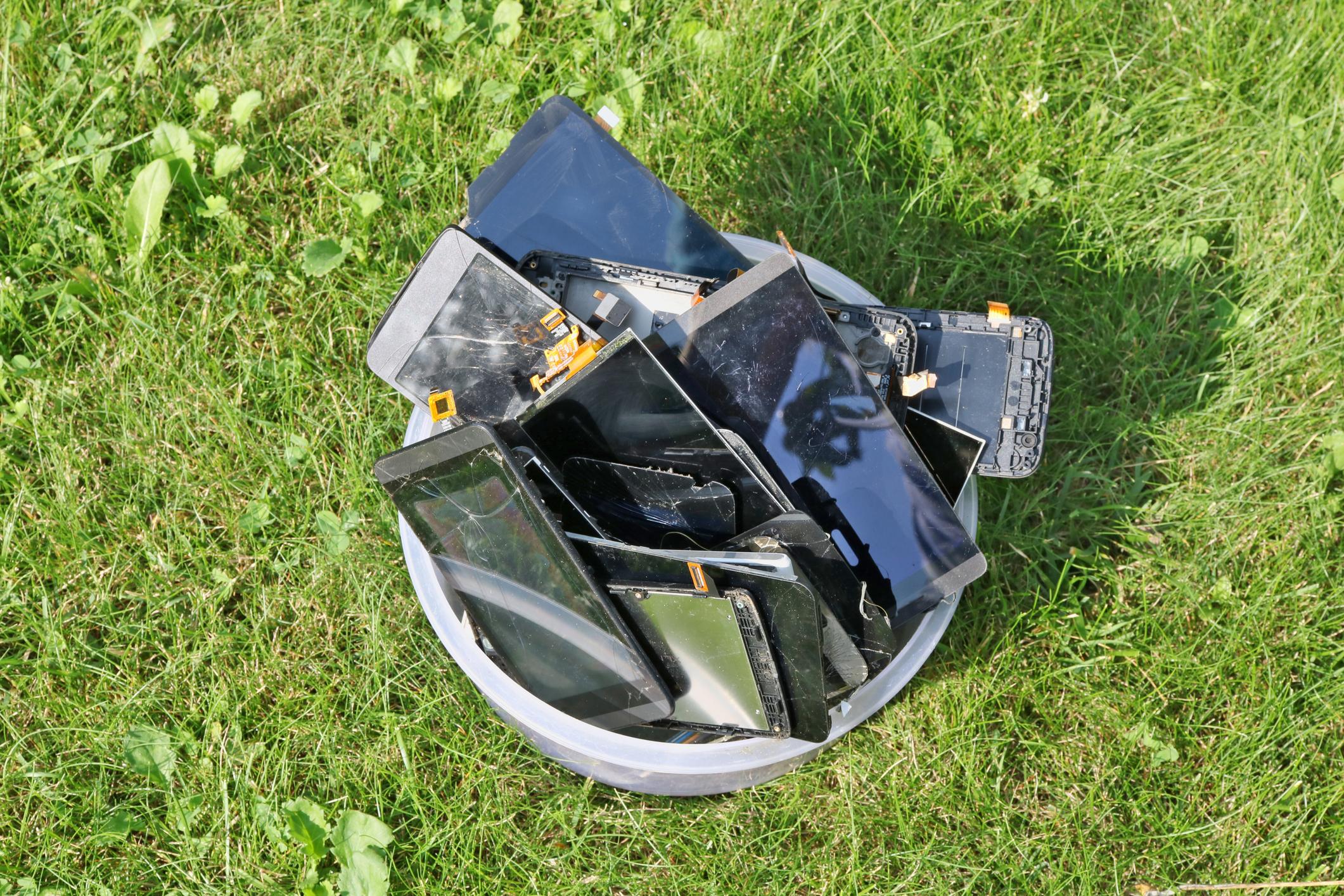 Broken mobile phones green grass