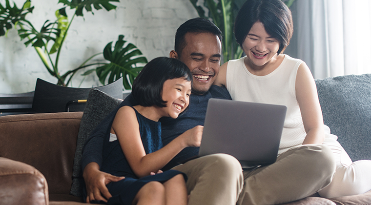 Family on the couch looking at a computer smiling