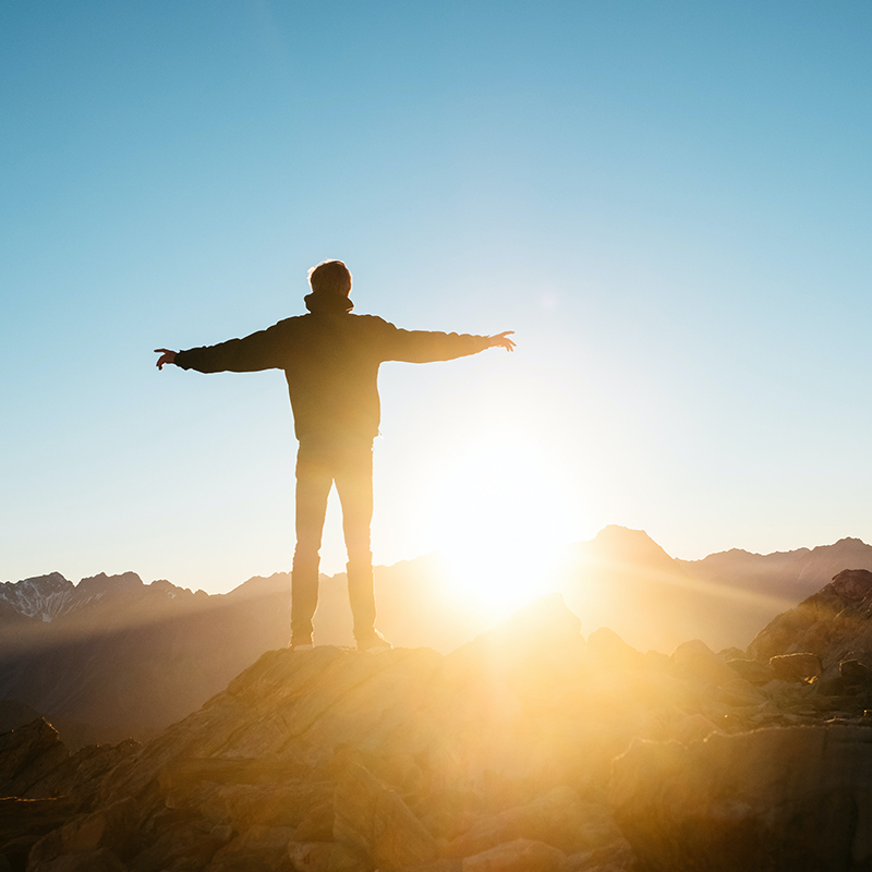 Freedom - a man standing on mountain during a sunset