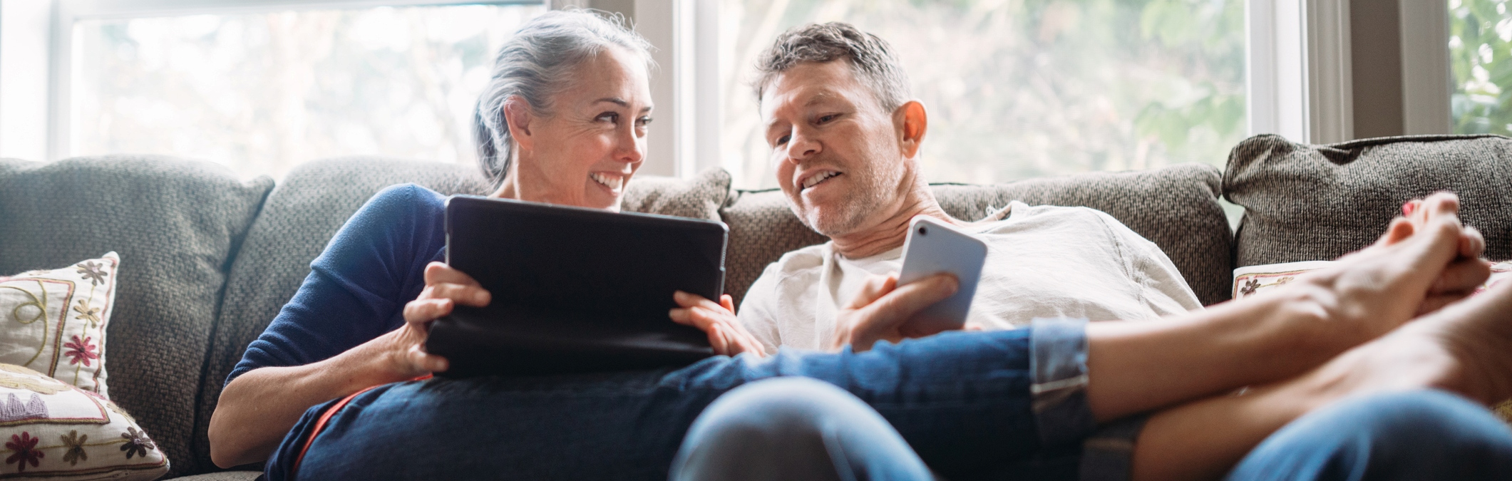 Couple sitting on the couch; woman is holding her tablet and man is holding his cellphone