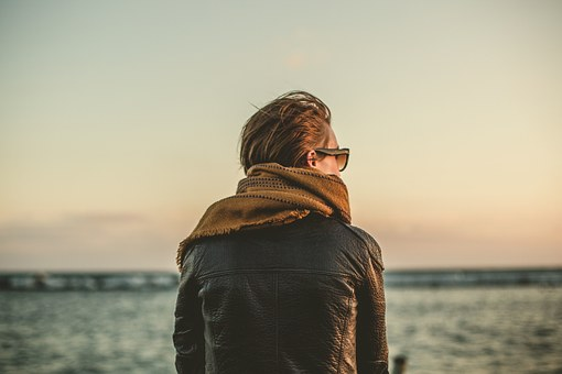 Mann med briller som ser på havet i solnedgang