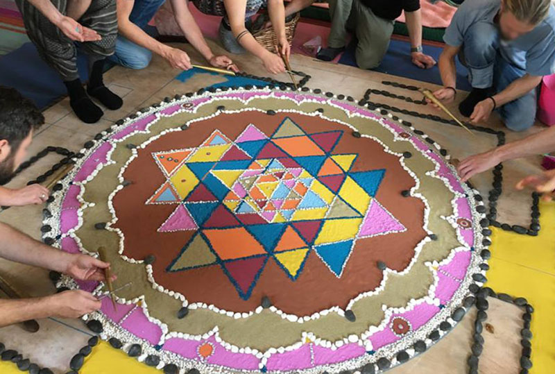 Group mandala nearing completion done with colored sands and seashells.