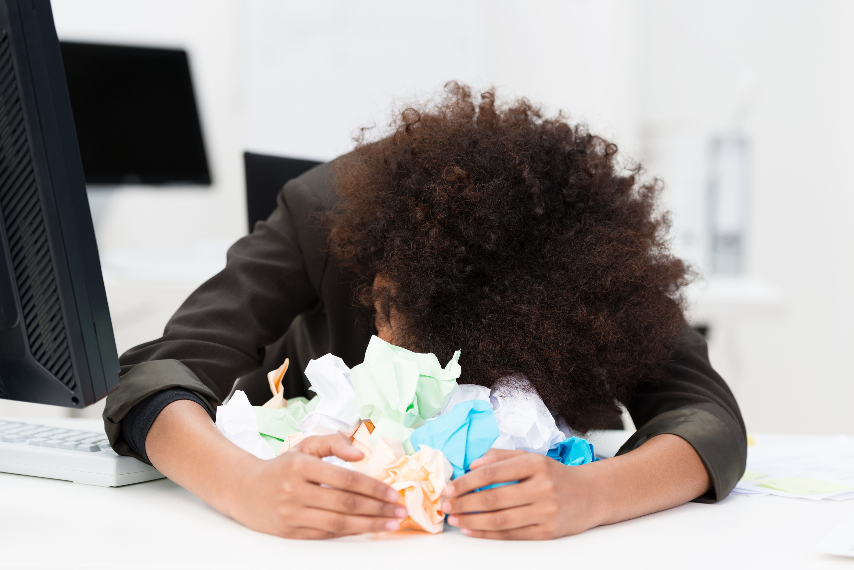Woman, with her head down and arms in front of her cradling a pile of crumpled up paper.