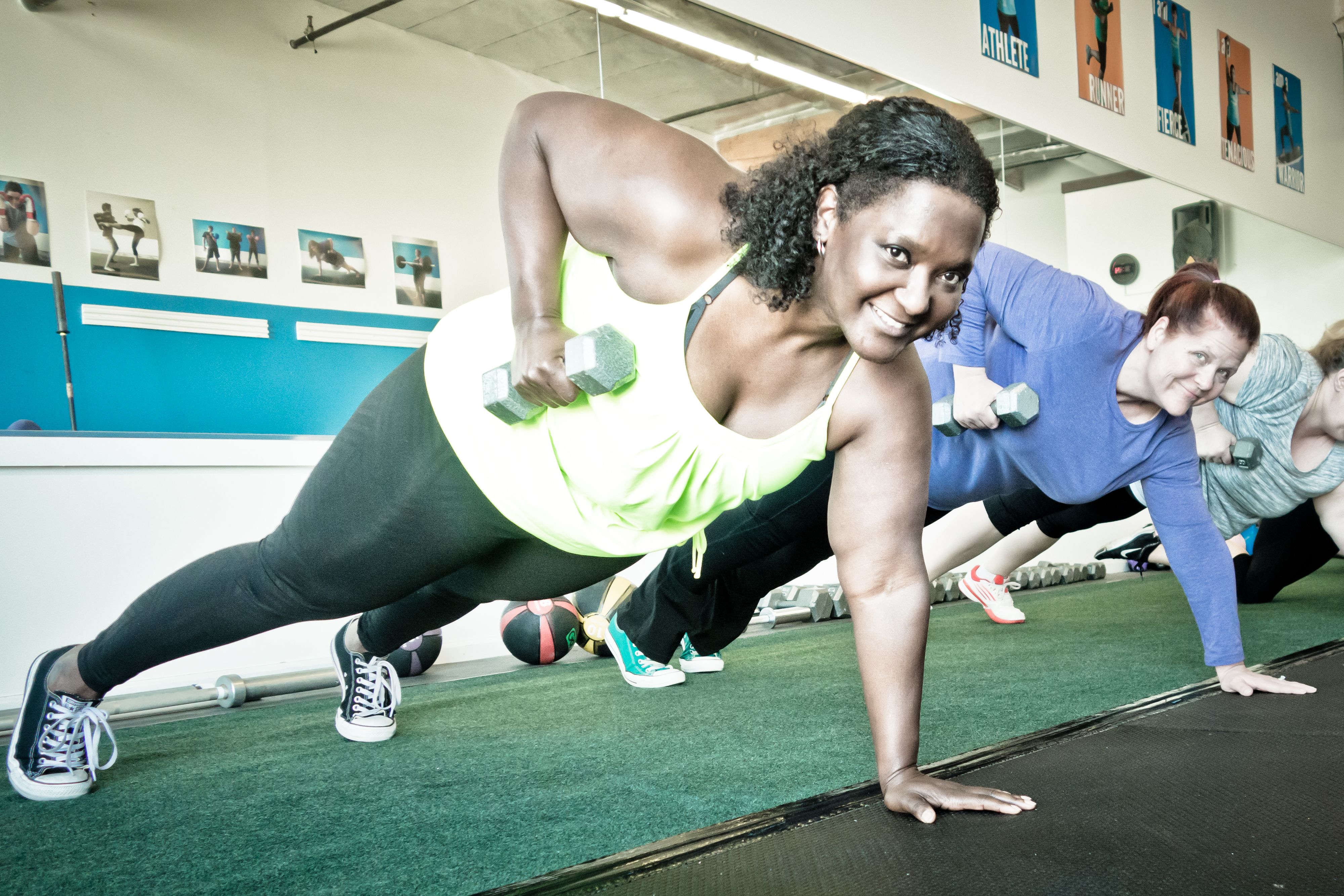 Women planking with dumbbells