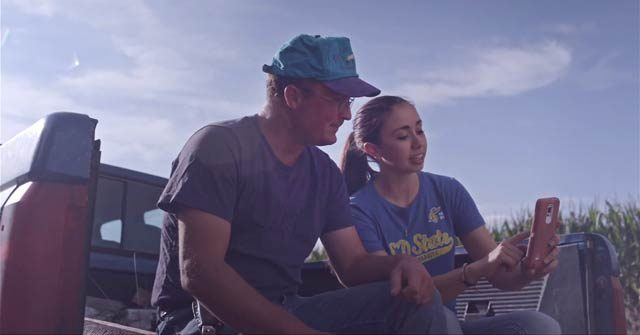Two people talking on a tailgate near a corn field