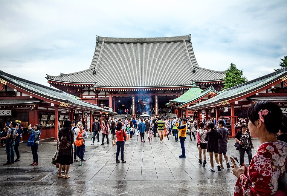 Crowd of people standing outside a temple.