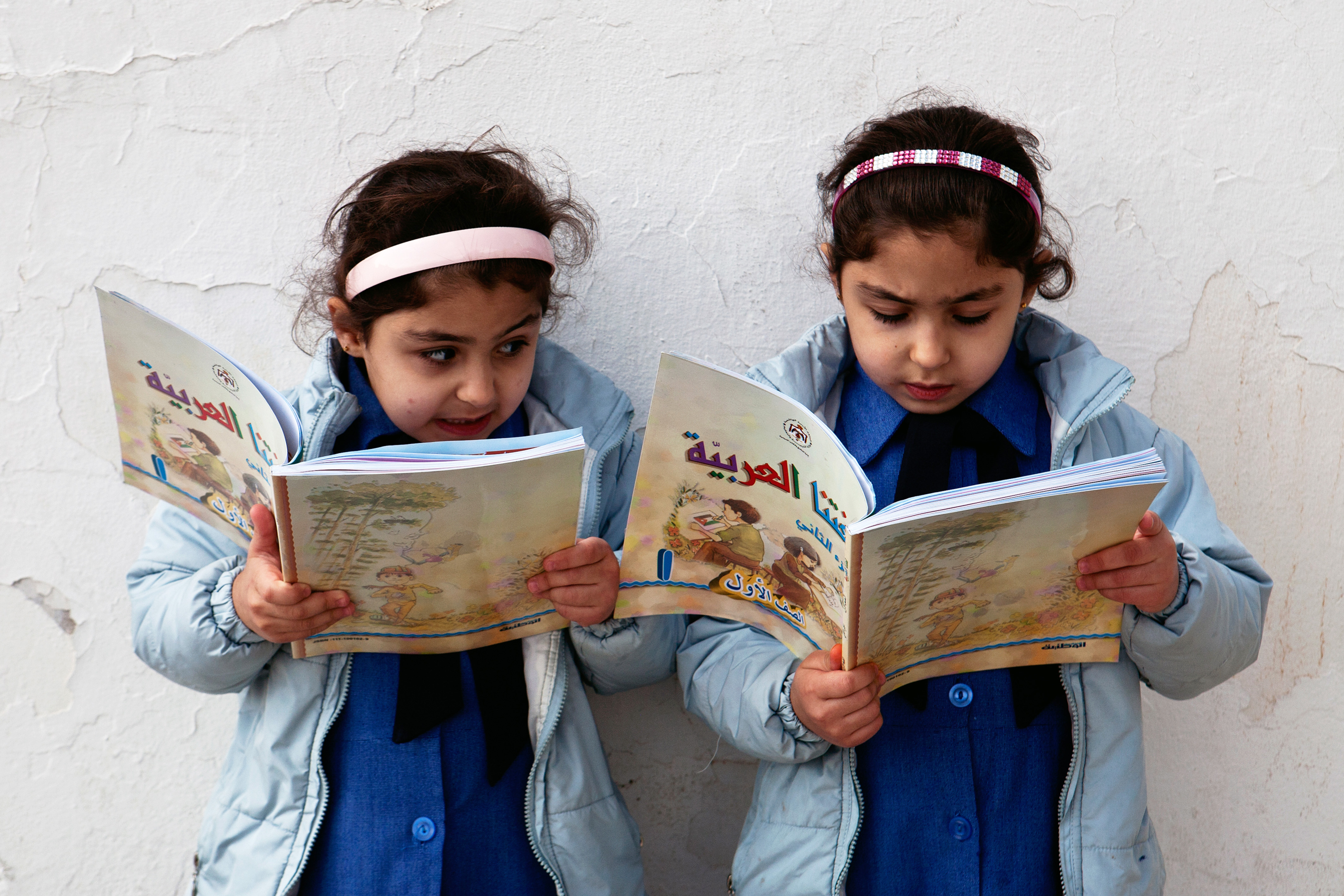 Two small girls reading a book.
