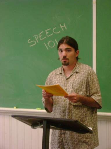 Man giving a speech in a classroom.