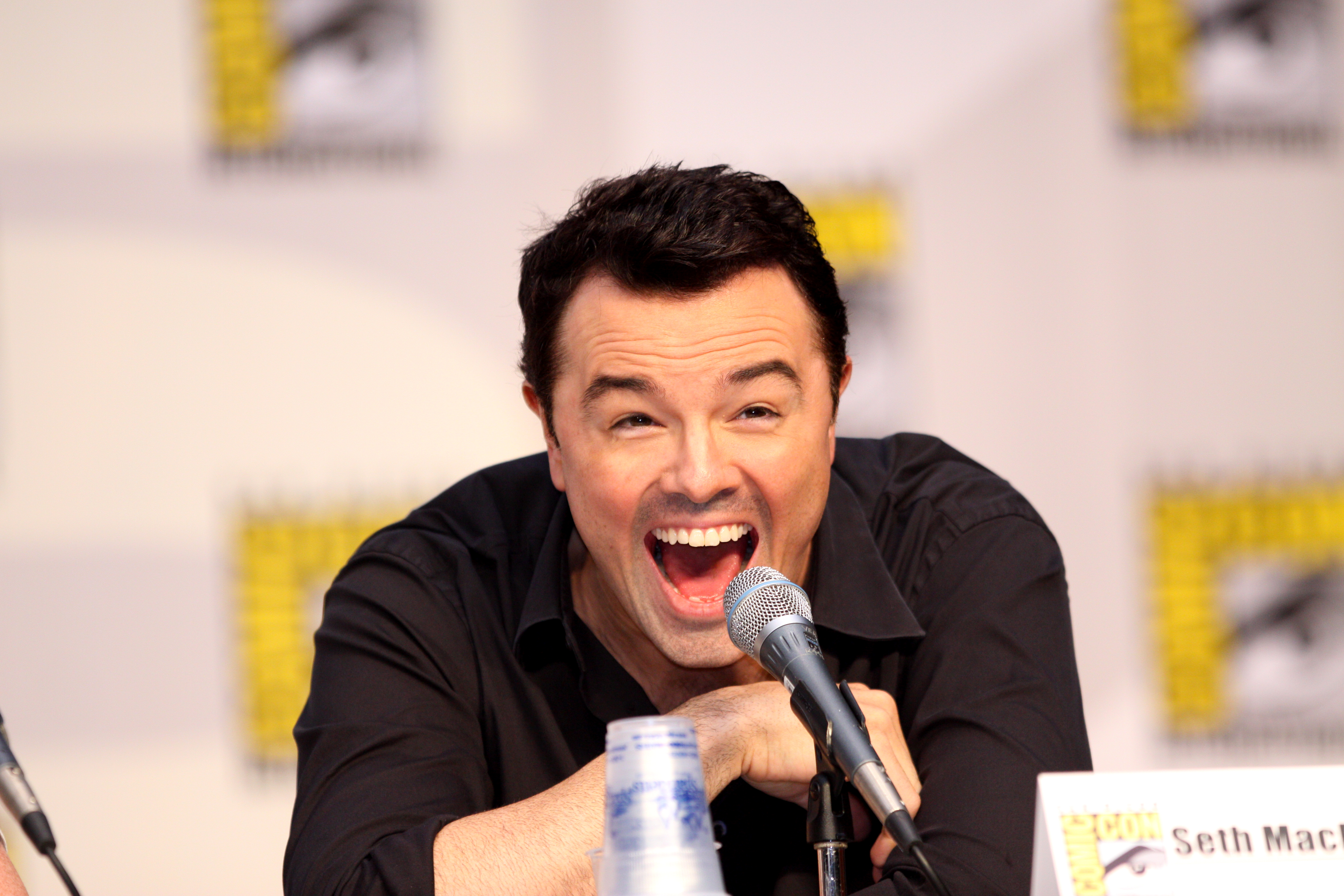 Comedian Seth MacFarlane answering questions at a press conference.