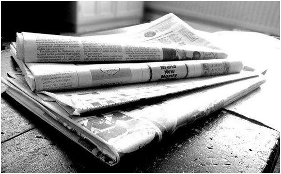 A stack of newspapers in black and white.