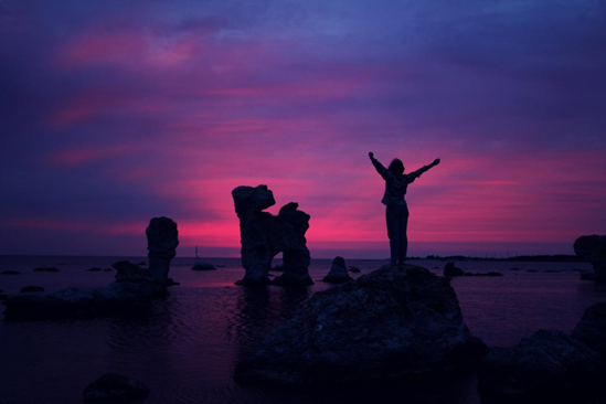Woman standing triumphantly on rock in front of sunset.