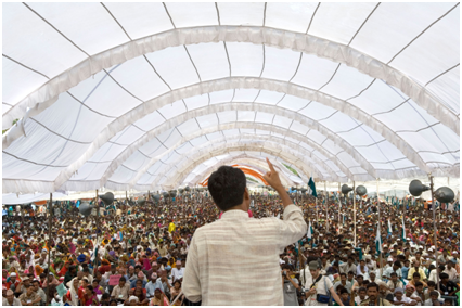 Back view of a man speaking in front of a large crowd under a domed tent.