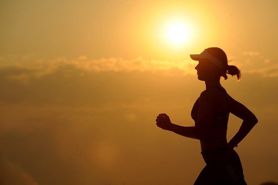 A woman jogging in front of a sunset.