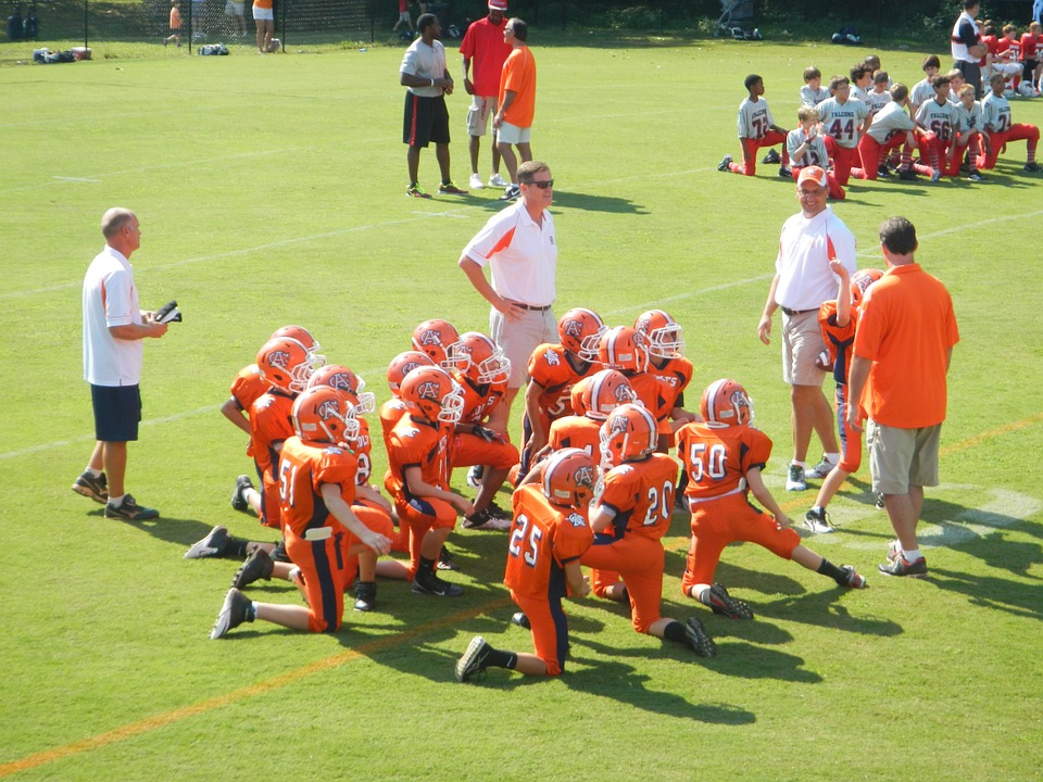 A group of American football players kneeling while listening to their coach.