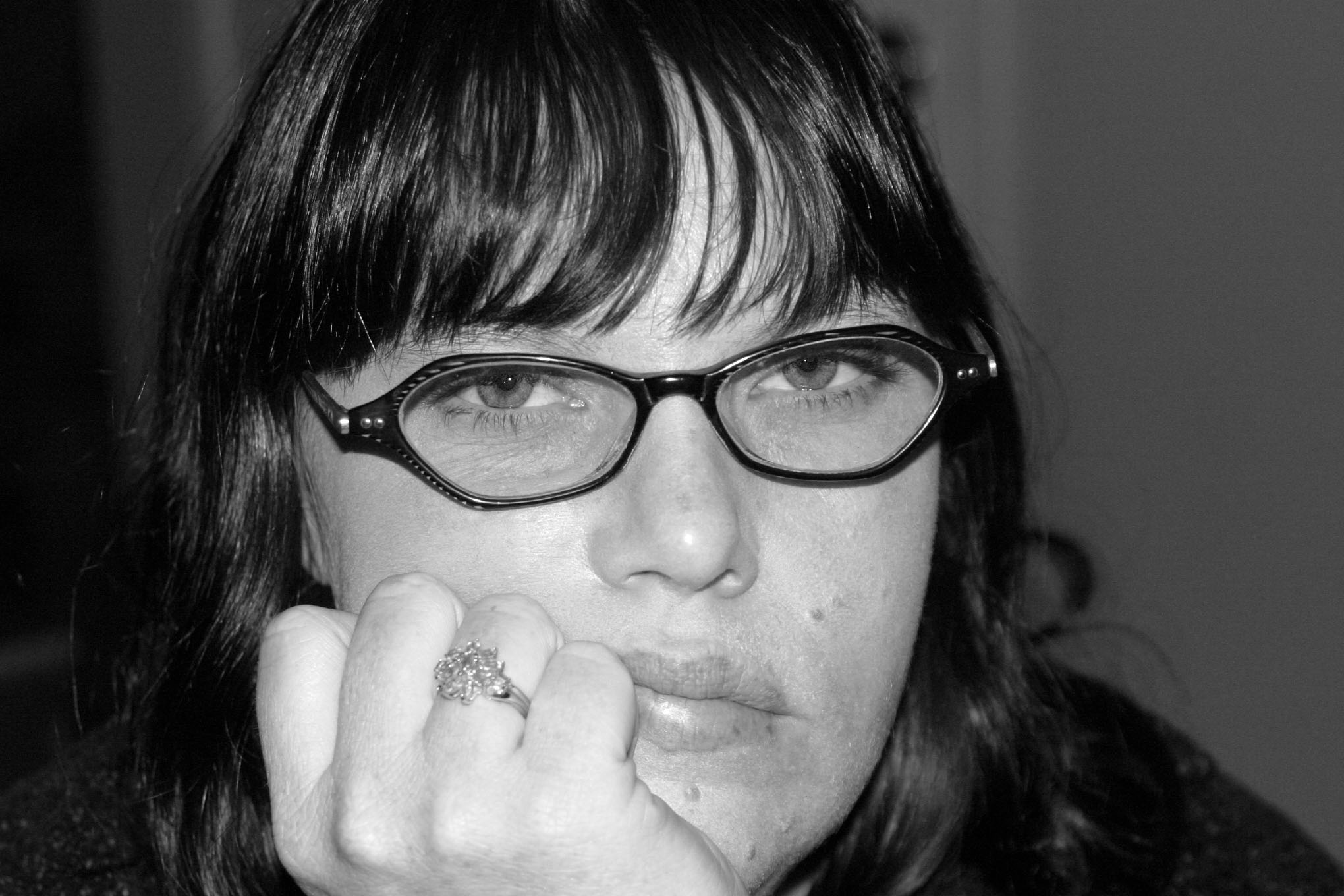 Photograph of a woman with her chin resting on her hand looking very bored.