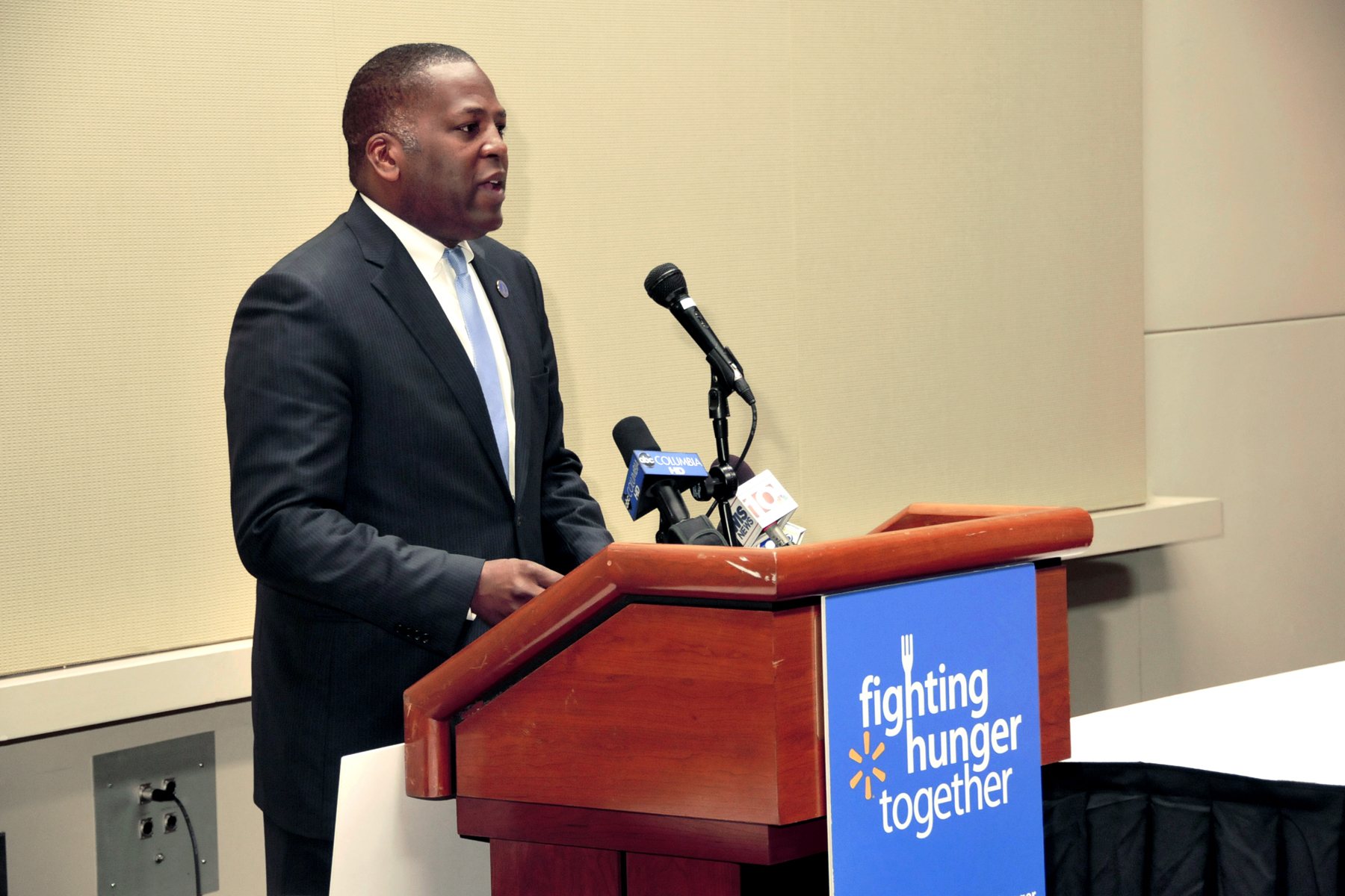 """A man speaking during Wal-mart's """"fighting hunger together"""" initiative."""