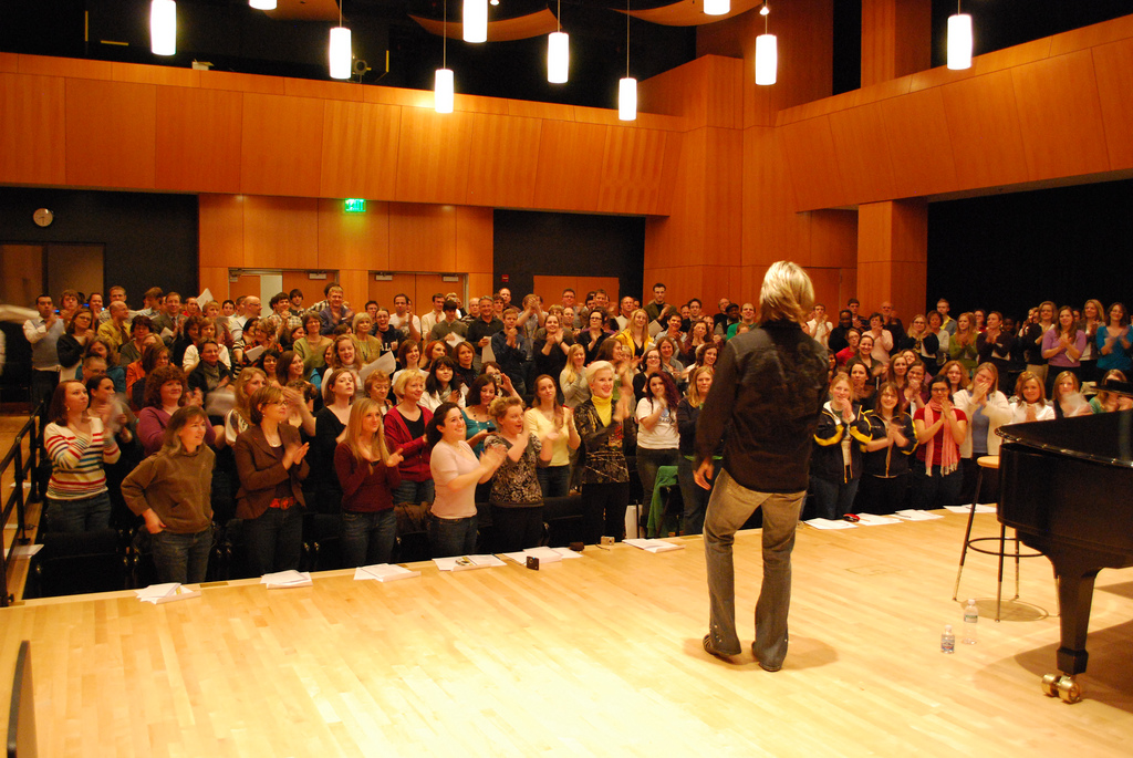 A speaker receiving a standing ovation from an audience.