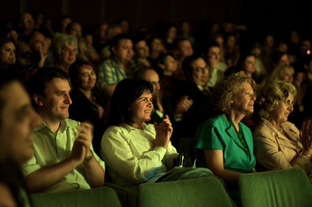 An audience clapping in a dark theatre.