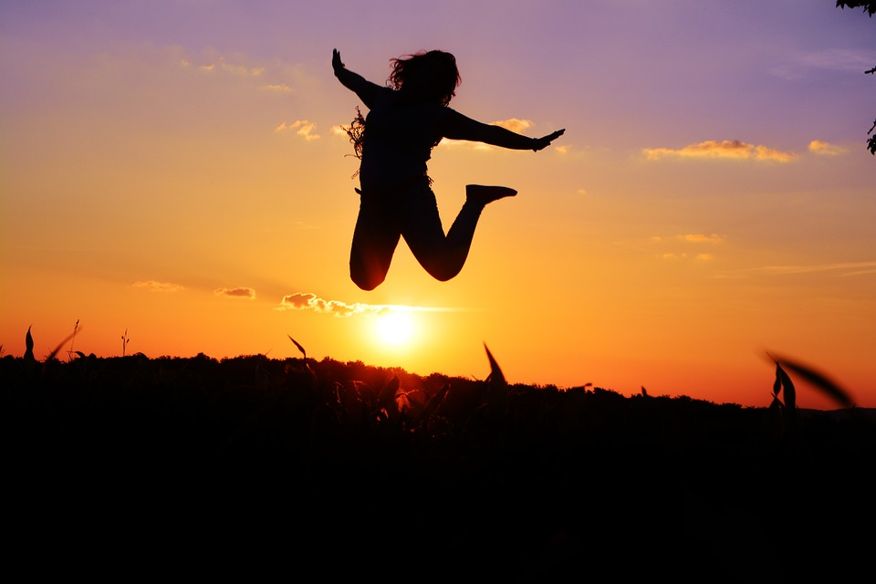 Woman jumping for joy in front of sunset.