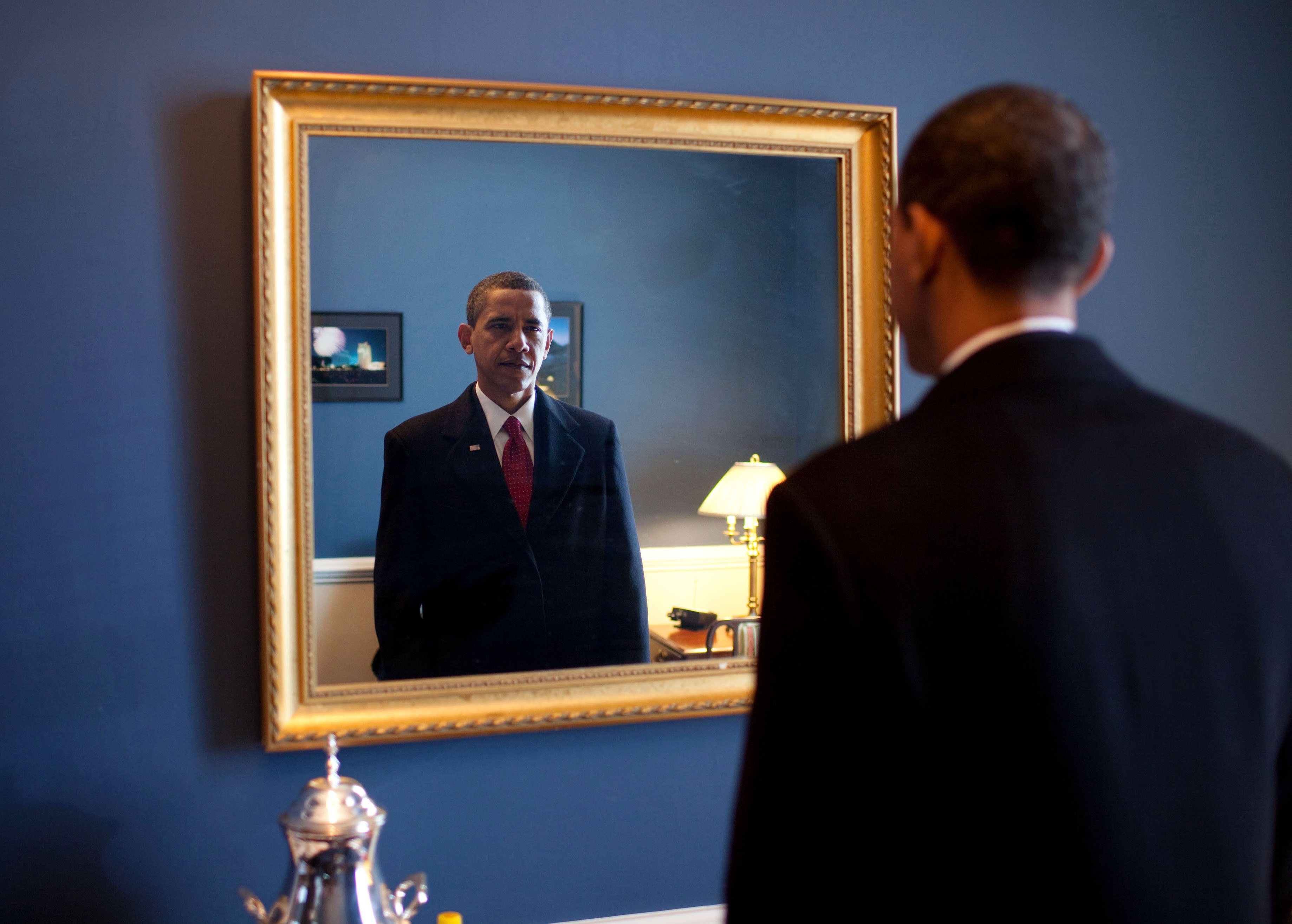 Former President Barack Obama standing in front of a mirror.