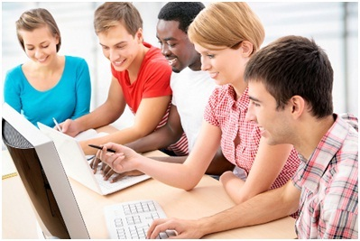 A group of five individuals smiling around a computer.