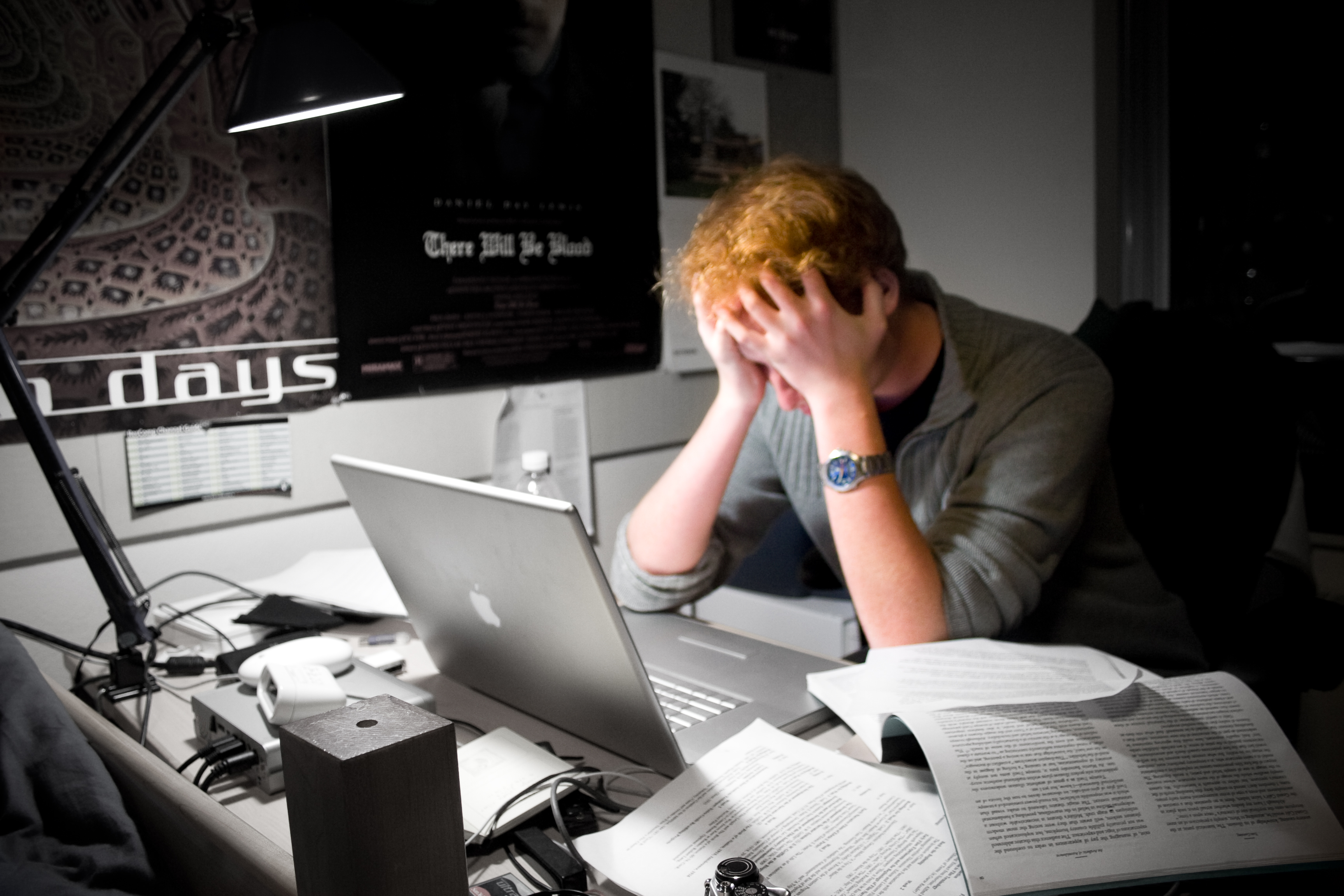 A visibly frustrated man with his head in his hands in front of his laptop and papers.