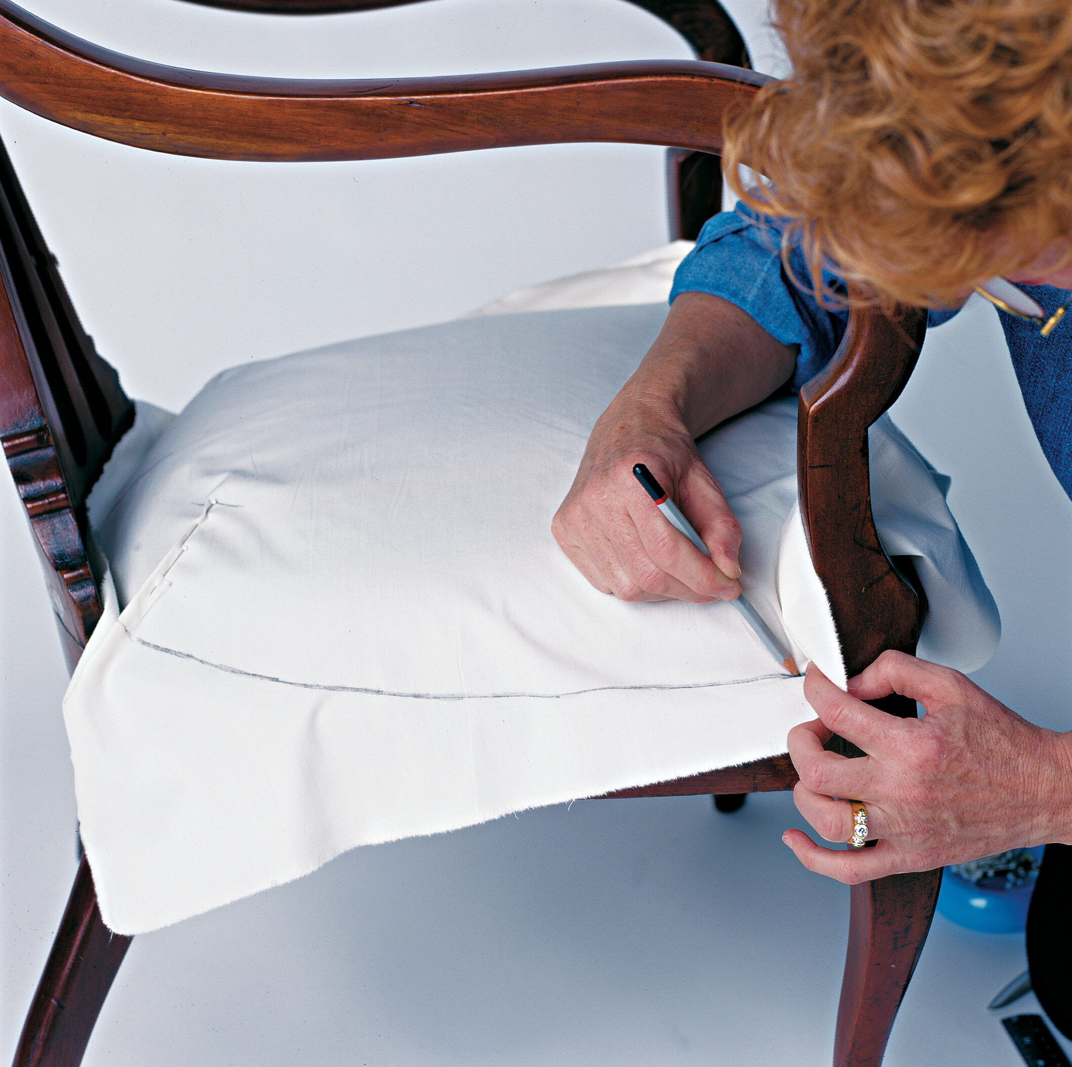 Smooth the fabric over the seat; pin folds, ripples, and puckers into darts where needed.
