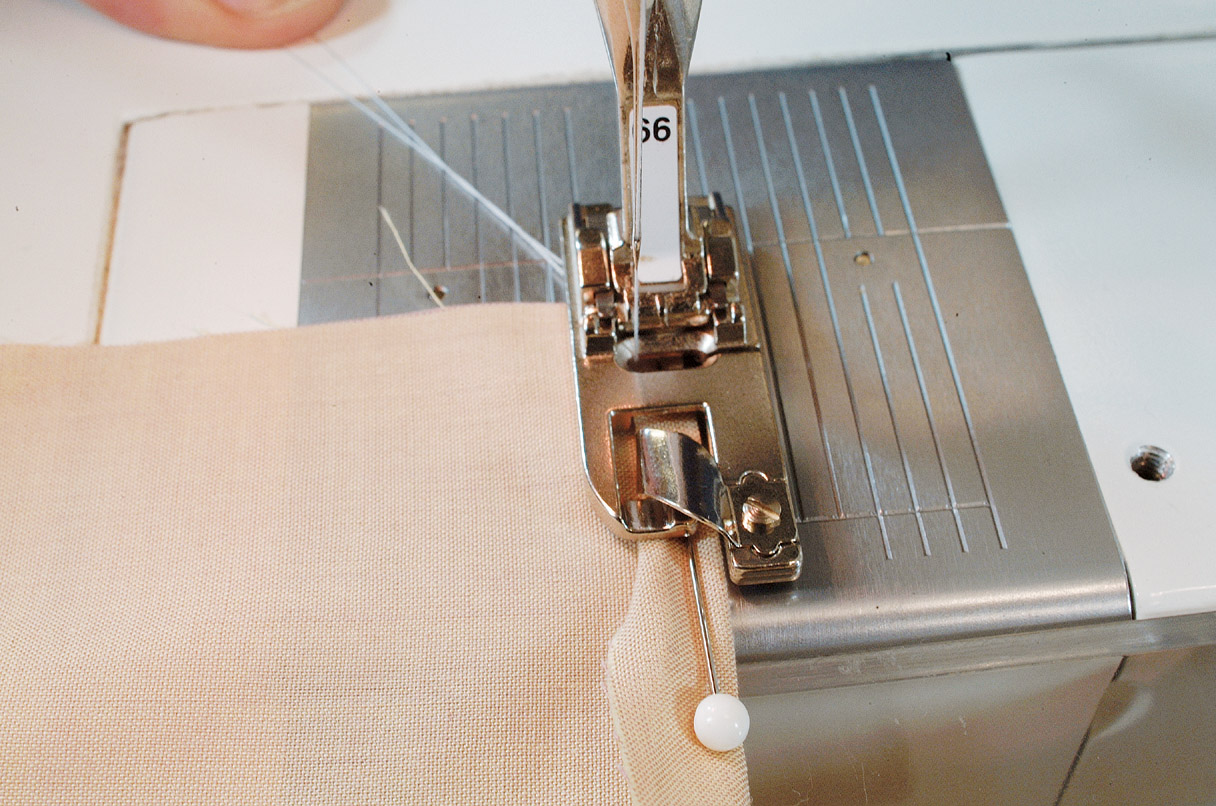 3. Position the pinned hem under the hemmer with the outer edge against the toe and lower the presser foot.